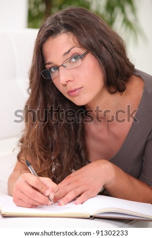 Thoughtful young woman writing in a book - stock photo