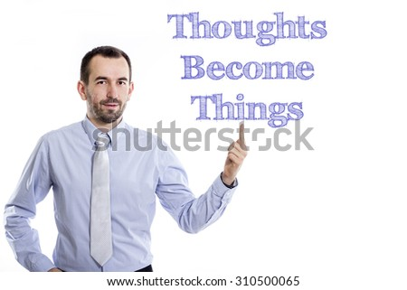 Thoughts Become Things - Young businessman with small beard pointing up in blue shirt