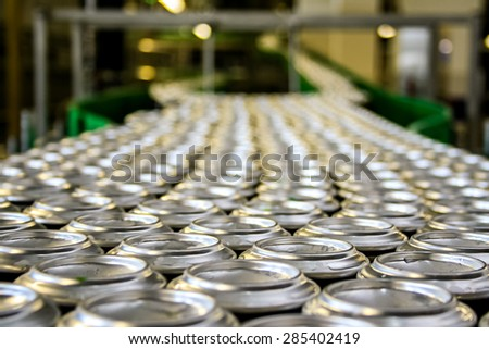 Thousands of beverage aluminum cans on conveyor line at factory. Concept of industrial power and growth - stock photo