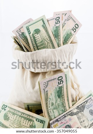 Thousands of US dollars pouring out of a cloth money bag onto a white background showing many currency notes or bills