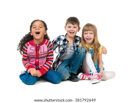 thre cheerful kids sitting on the floor in a studio isolated on white background - stock photo