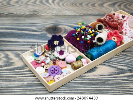 thread and material for handicrafts in box on a wooden background - stock photo