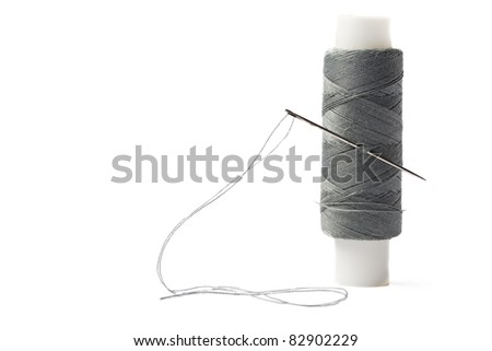 Thread bobbin and needle on white background - stock photo