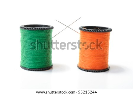 Thread bobbins with needles embraced in a duel - stock photo