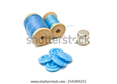 thread, buttons and thimble on white background closeup - stock photo