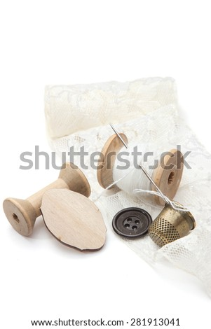 thread for sewing on wooden spools with needle, empty spool of thread, buttons, metal thimble, and a piece of lace on a white background, retro style - stock photo