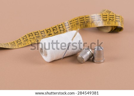 Thread, needle, thimble and measuring tape - stock photo