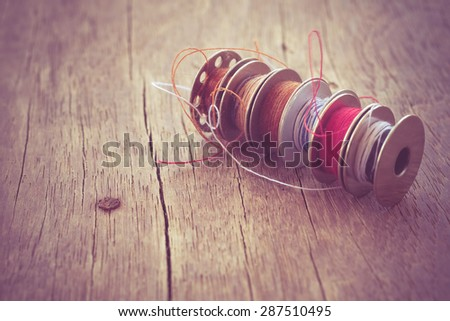 thread rolls on wood background with filter effect retro vintage style - stock photo