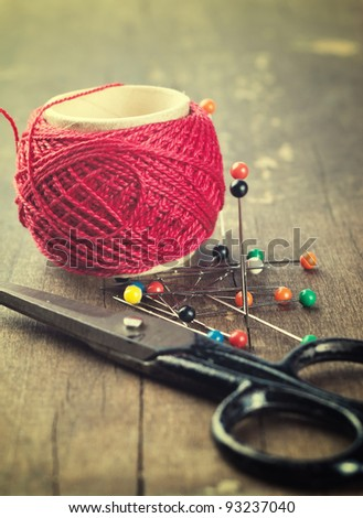 thread, scissors and needles on wooden table - stock photo