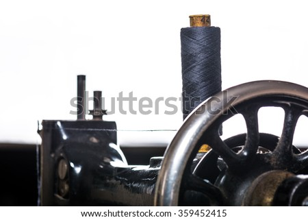 Thread spool on a old vintage sewing machine. Selective focus - stock photo