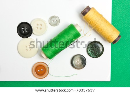 thread with a needle and buttons on the background of the notebook - stock photo