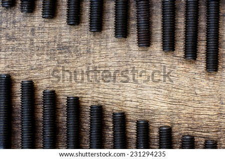 threaded bolt arrangement stratified position in the old cracked wooden background - stock photo