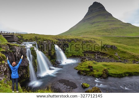 Threaded full-flowing waterfall Kirkjufell Foss on the grassy mountains. Middle-aged woman tourist admires the beauty of nature - stock photo