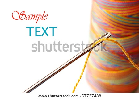 Threaded needle with multicolored spool of thread in background on white with copy space.  Macro with shallow dof. - stock photo