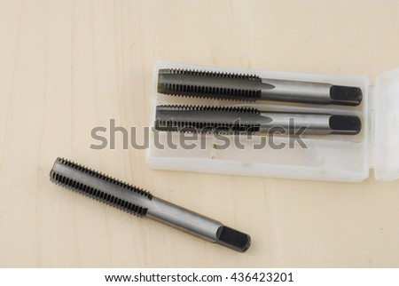 Threading hand tap on wooden background. Cutting tools