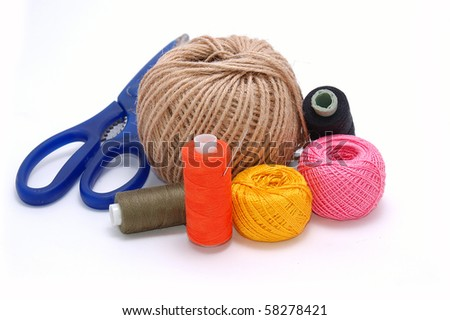Threads, a needle and scissors close up on a white background - stock photo