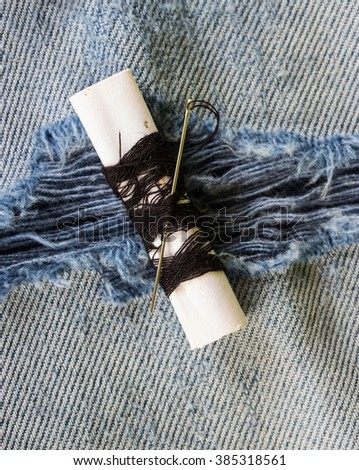 Threads and needle on jeans backround, wear repair concept - stock photo