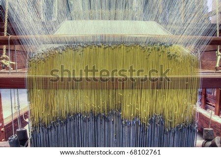 Threads hanging under a damask weaving machine - stock photo