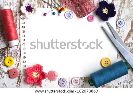 threads, measuring tape, pins, buttons on a wooden background - stock photo