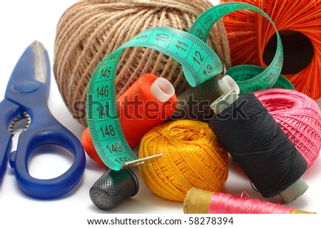 Threads, needle and scissors close up on a white background
