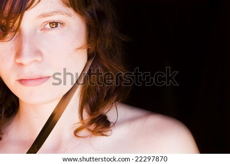 Threatened woman against black background. Gender violence. - stock photo