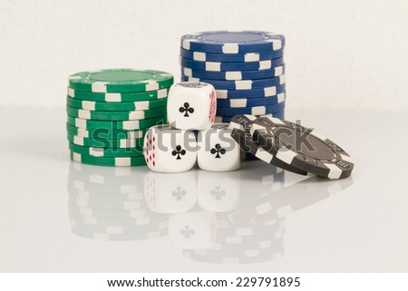 Three Aces and Green, Blue, Black Playing poker dice closeup on white background reflective - stock photo