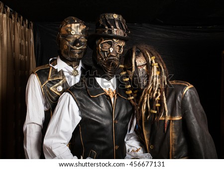 Three actors in cyborg costumes against black wall