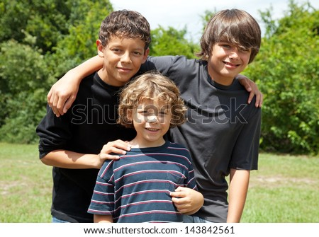 Three adorable boys, two adolescent friends and one little brother smiling. Diversity.   The two brothers are mixed race. - stock photo