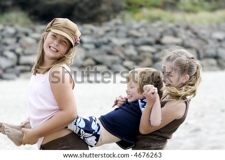 Three adorable children playing together at the beach with big smiles on their faces - stock photo