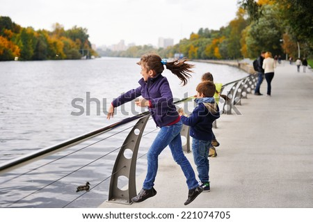 Three adorable fashionable children two school aged girls and a boy have fun and feeding ducks on the beauty autumn dai in the park - stock photo