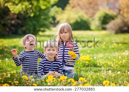 Three adorable kids, dressed in striped shirts, hugging and smiling, sitting on the grass in a dandelion field - stock photo