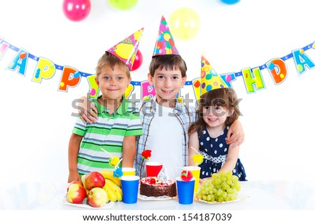 Three adorable kids having fun at birthday party