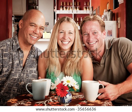 Three adult friends smiling in a coffee house