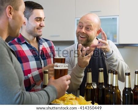 Three adult male friends with glasses of beer and chips at the kitchen - stock photo