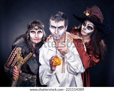 Three adults dressed in Halloween costumes. - stock photo