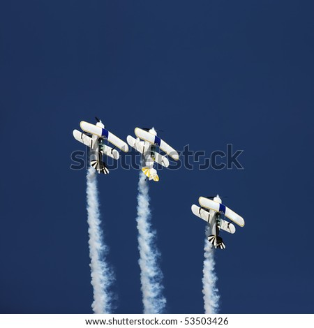 Three aerobatic aeroplanes flying straight up during an airshow - stock photo