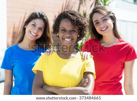 Three african american and caucasian girlfriends in colorful shirts - stock photo