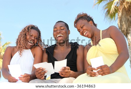 Three African American Friends Outdoors Looking at Photographs and Laughing - stock photo