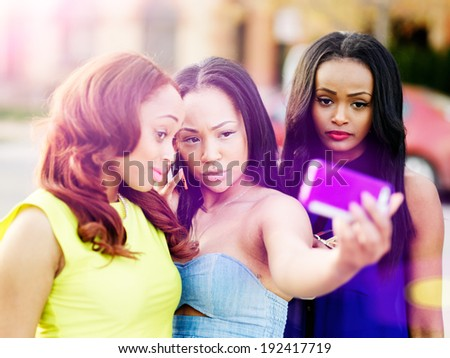 three african girls taking selfies with smart phone - stock photo
