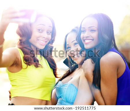three african girls taking selfies with smart phone with lens flare in background. - stock photo