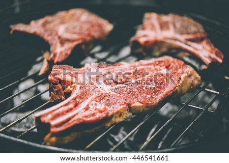 Three aged rib-eye beef meat steaks cooking. Grill and BBQ or barbecue season concept. Toned image