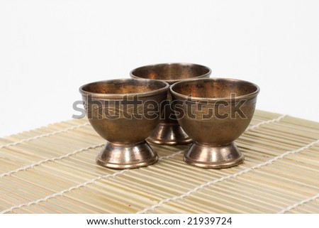 Three aged steel cups on bamboo mat