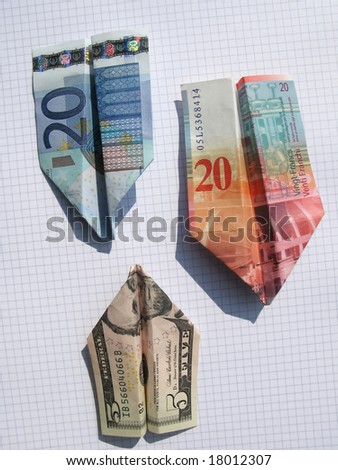 Three airplanes made of euro, dollar and swiss frank on squared paper - stock photo