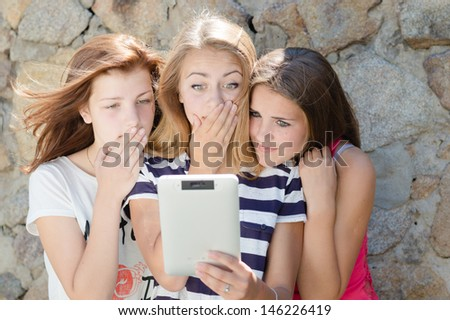 Three amazed teen girl friends looking on tablet pc on summer day - stock photo