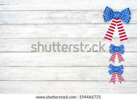 Three American Flag Glitter Bows on side of Rustic White or Gray Wood Board Background with room or space for copy, text,  Horizontal - stock photo