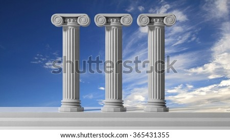 Three ancient pillars with blue sky background. - stock photo