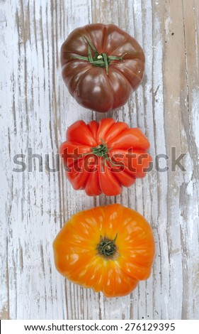 three ancient tomatoes variety on wooden table  - stock photo