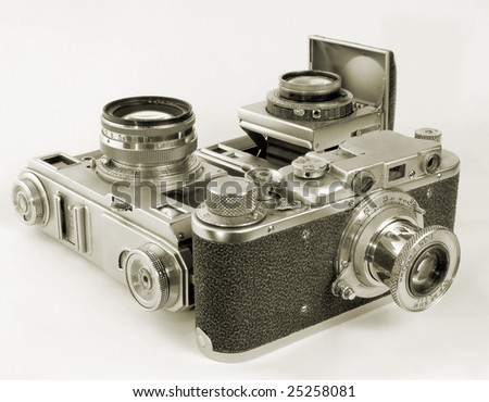 Three antiquarian 35-mm film cameras with put-forward lens. - stock photo