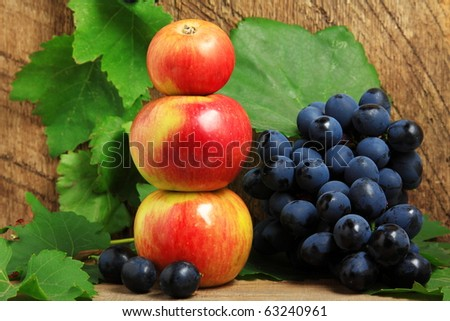 Three apples and bunch of grapes on wooden background - stock photo
