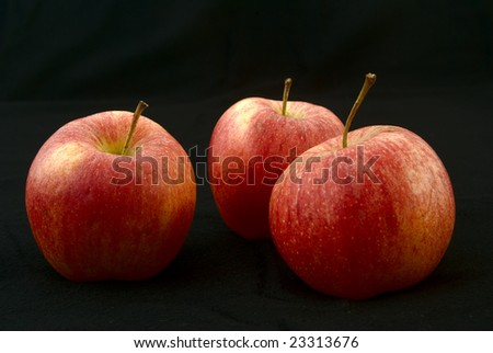 three apples come out from the dark - stock photo